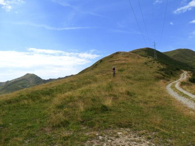 Traccia di sentiero che scende dal San Jorio seguendo il crinale erboso