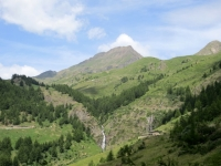 In primo piano l'Alpe di Moron con la vicina cascata, sullo sfondo il Monte Fallère